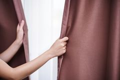 Closeup of women hand opening curtain Royalty Free Stock Image