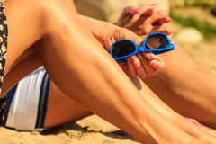 Closeup of women legs sun tanning on beach. Royalty Free Stock Photos