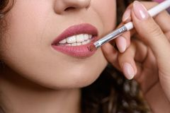 Closeup of hand of makeup artist drawing woman lips royalty free stock photography