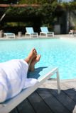 Closeup of women's feet relaxing by swimming pool Stock Images