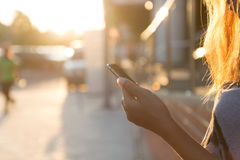 Closeup women using smartphone at sunset Stock Photo