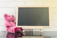 Closeup wood black board with pink bear doll on black glass table and white brick wall textured background with sunlight Royalty Free Stock Photo