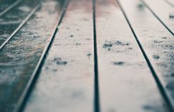 Closeup of wood planks while raining in perspective. Background of wooden natural surface and raindrops. Wet wood royalty free stock photography