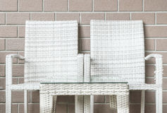 Closeup wood weave table and wood weave chair on blurred brown brick wall texture background , beautiful interior in relaxation of Royalty Free Stock Images