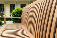 Closeup Wooden Bench. With Green Bush and Yellow Building Background Stock Photo