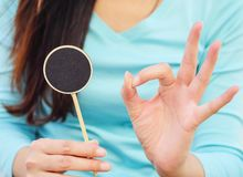 Closeup wooden black board in circle shape with hand of woman in okay meaning. Closeup wood black board in circle shape with hand of woman in okay meaning stock photography