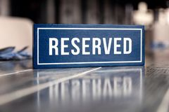 Closeup wooden blue white rectangular plate with the word Reserved standing on gray table in restaurant. Ð¡oncept of preparation royalty free stock photography