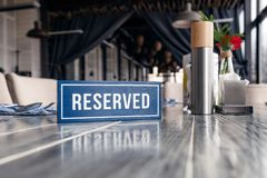 Closeup wooden blue white rectangular plate with the word Reserved standing on gray vintage table in restaurant near to setting, stock photo