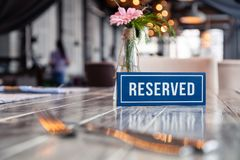 Closeup wooden blue white rectangular plate with word Reserved standing on gray vintage table in restaurant near to setting, stock image