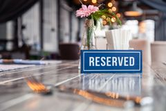 Closeup wooden blue white rectangular plate with word Reserved standing on gray vintage table in restaurant near to setting,. Closeup wooden blue white royalty free stock image