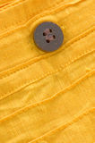 Closeup of wooden button on yellow organic cotton Royalty Free Stock Photography