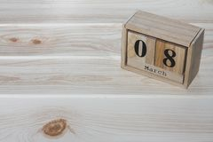 Closeup wooden calendar with black March 8th word on wood desk stock photos