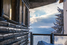 Closeup of wooden chalet wall against winter landscape Royalty Free Stock Photo