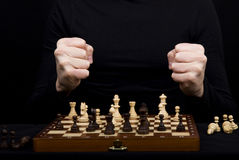 Closeup of a wooden chess board with chess figures and the man' Royalty Free Stock Photo