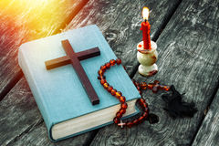 Closeup of wooden Christian cross on bible, burning candle and prayer beads on the old table. Royalty Free Stock Photography