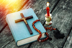 Closeup of wooden Christian cross on bible, burning candle and prayer beads on the old table. Stock Image