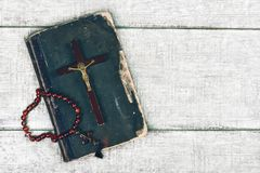 Closeup of wooden christian cross and bible on the old wooden background. Church utensils royalty free stock photos