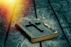 Closeup of wooden Christian cross on bible on the old table. Stock Photo