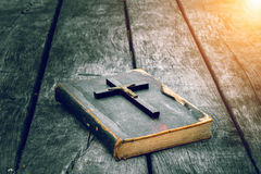 Closeup of wooden Christian cross on bible on the old table. Stock Images