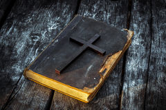 Closeup of wooden Christian cross on bible on the old table. Church utensils stock images