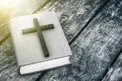 Closeup of wooden Christian cross on bible on the old table. royalty free stock image