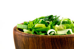 Closeup from wooden dish with leek. On white background royalty free stock images