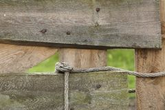 Wooden fence and rope. A closeup of a wooden fence and a piece of rope. This fence is the entrance to a meadow royalty free stock image