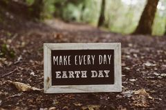 Chalkboard with the text make every day earth day. Closeup of a wooden-framed chalkboard with the text make every day earth day written in it, on the ground in Royalty Free Stock Images