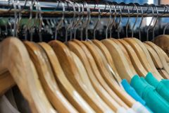 Closeup of wooden hangers in a fashion store. Unisex clothes of blue color. Concept for shopping design and sales. stock photos