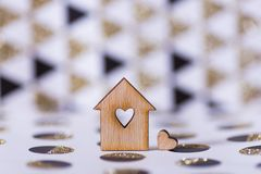 Closeup wooden house with hole in form of heart on geometric abstract background with golden glitter. Concept of sweet home, copy space royalty free stock image