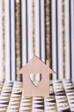 Closeup wooden house with hole in form of heart on geometric abstract background with golden glitter. Concept of sweet home, copy space royalty free stock photo