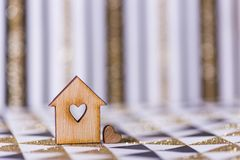 Closeup wooden house with hole in form of heart on geometric abstract background with golden glitter. Concept of sweet home, copy space royalty free stock photography