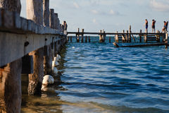 Closeup of wooden pier, blue water. Teens standing on the pier fishing in the ocean Royalty Free Stock Photo