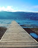 Closeup of wooden pier on the lake. Shore with forest and snow covered mountains and blue sky background Stock Images