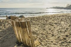 Closeup of wooden poles, standing at the beach , leading to the. Wooden post on the beach leading ti the sea , blue sky with clouds royalty free stock photos