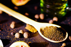 Closeup wooden rustic spoon filled up with fresh herbal tea powder, other teas and spices in background, very nice stock photo
