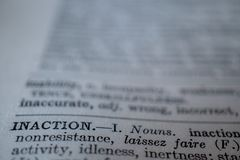 Closeup of the word inaction. A macro of the word inaction with sharp focus and blurred background Royalty Free Stock Photo