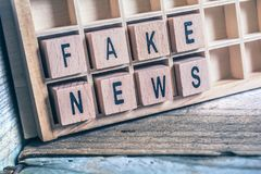 Closeup Of The Words Fake News Formed By Wooden Blocks In A Type. A Closeup Of The Words Fake News Formed By Wooden Blocks In A Type Case royalty free stock photo