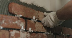 Closeup worker applying brick cuts tile to the wall. Wide photo Stock Photo