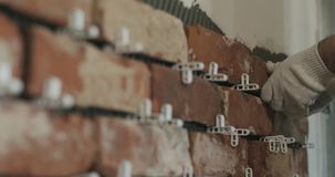 Closeup worker applying brick cuts tile to the wall. Wide photo Stock Photos