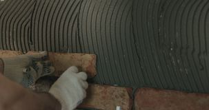 Closeup worker applying brick cuts tile to the wall. Wide photo Royalty Free Stock Images