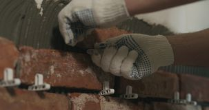 Closeup worker applying brick cuts tile to the wall. Wide photo Royalty Free Stock Photos