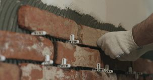 Closeup worker applying brick cuts tile to the wall. Wide photo Royalty Free Stock Image