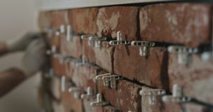 Closeup worker applying brick cuts tile on the wall. Wide photo Royalty Free Stock Photography