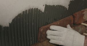 Closeup worker applying brick cuts tile on the wall. Wide photo Royalty Free Stock Image