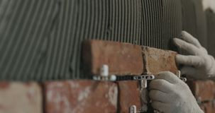 Closeup worker applying brick cuts tile on the wall. Wide photo Stock Photography