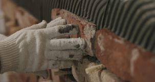 Closeup worker applying brick cuts tile on the wall. Wide photo Royalty Free Stock Photo