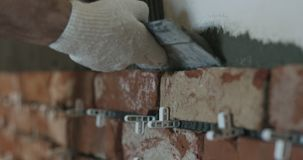 Closeup worker applying concrete glue to wall before applying brick tile. Wide photo Royalty Free Stock Photography