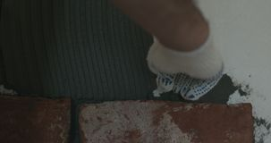 Closeup worker applying concrete glue to wall before applying brick tile. Wide photo Royalty Free Stock Image