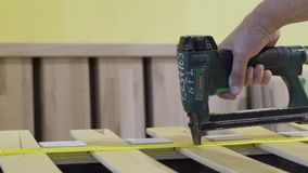 Closeup of worker holds board with stapler. Action. Worker uses stapler to bond tape with wood boards in furniture. Factory stock footage